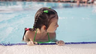 Little girl having fun in a swimming pool, first time learning to swim, spending summer holidays on a beach resort