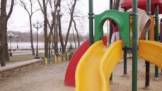 little girl in spring Park with rolls of bright-colored slides