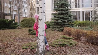 little girl is playing hide and seek in an autumn park.