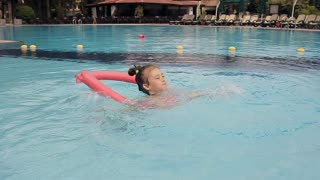 Little Girl Learning To Swim With Float And Armbands. Outdoor Pool In The Summer
