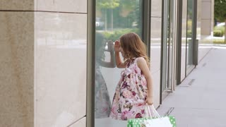 Little Girl looks at the window near the shopping center.