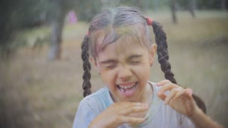 little girl smeared with colours of Holi laughs and enjoys the water splash in the face