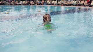 Little kid girl swim in a swimming pool clear water on summer resort
