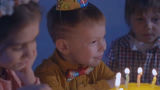 little kids sit at red table with cake and blow in multicolor party blowers at birthday party. Happy group of children at birthday party.