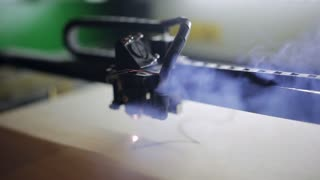 Machine for laser cutting wood close up cuts chipboard and the smoke appears.