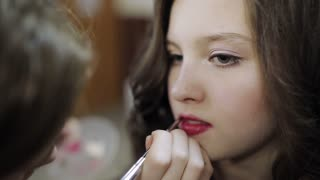 makeup artist paints lips to the teenager girl in the beauty salon