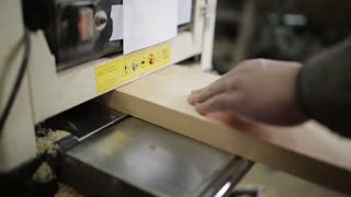 Male carpenter working with planing machine in workshop