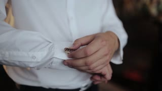 Man buttoning cuff link on the shirt close-up. Businessman buttoning cuff sleeves shirt standing near the window.