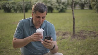 man is sitting on the lawn drinking coffee and talking on the phone