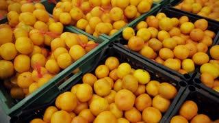 Many fruits mandarins lying in boxes in supermarket. orange fruit on the market