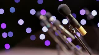 many microphones on stage in the rays of twinkling lights