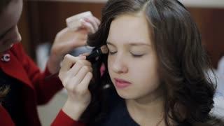 Master makeup artist at the beauty salon does makeup girl teenager