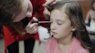 master makeup artist paints the eyes of the little girl