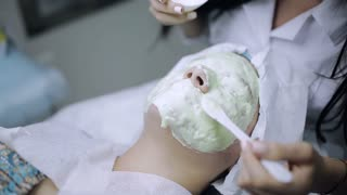 Medical mask smeared on the face of the woman with skin problems. Beautician in beauty salon for women spread a face mask on the client skin.