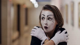 mime with a white make-up on her face shows different emotions