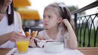 Mom feeds naughty girl soup in the restaurant outdoor
