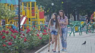 Mom helps my daughter with a broken leg on crutches to walk along the street