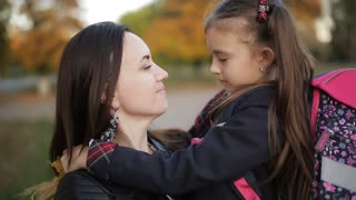 Mom hugs the little girl and looking at the camera. Mother and daughter after school in the fall.