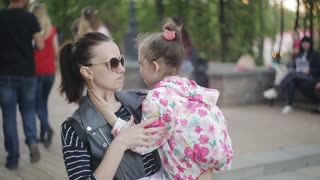 mom is on the hands of upset little girl on a crowded street