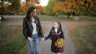 Mother and a little girl with a backpack on shoulders and a bouquet of yellow autumn leaves in hand back home from school. Mother and daughter walking hand in hand from school after school.