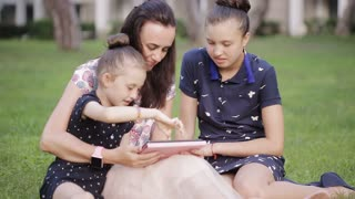 mother and daughter on the grass with tablet. mom reads a story to two daughters in the meadow