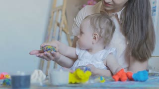 Mother and girl make figures of plasticine and kinetic sand
