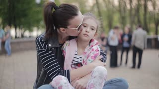 Mother comforting her upset daughter in the Park