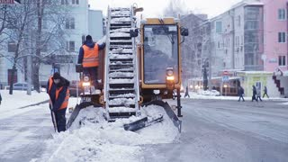 municipal snow removal machine grabs snow from the street