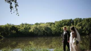 Newlyweds walking around the lake
