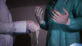 Nurse helps the doctor to put on white medical gloves