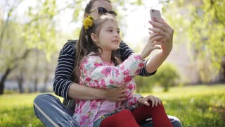 Photo selfie family - mother and little child daughter hugging kissing shooting pictures via smart phone during walking in park