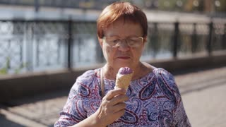Portrait of an elderly woman eating ice cream in a waffle cone standing on the waterfront
