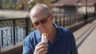 Portrait of Elderly man eating ice cream in a waffle cone in front of the camera