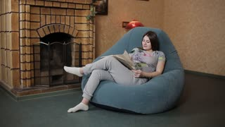 Pregnant woman reading book while sitting on sofa