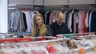 pregnant woman with her husband in a children's clothing store. Happy family choose clothes for baby