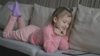 Pretty little girl lying on sofa using tablet . Small child playing on the laptop on an orange couch at home. A little girl watches cartoons in the computer
