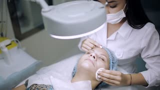 Professional beautician applying cosmetic mask on female face at beauty salon.