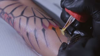 Professional tattoo artist makes a tattoo on a young girl's hand in slow motion. Tattoo artist make tattoo at the studio,close up