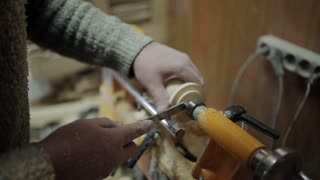 Sanding wood on a lathe. Foot operated spring pole wood lathe.