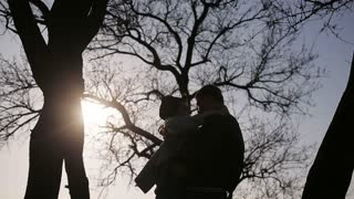 Silhouettes of smiling young couple at sunset