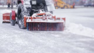 Snow plow outdoors cleaning street. snowplow removing fresh snow from city square