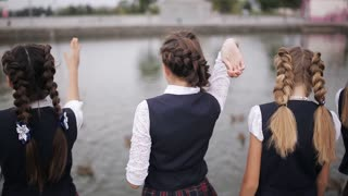Students in school uniform feeding ducks in a pond in the school yard. Girls College coeds wearing the same school uniform feed the ducks in the pond on campus