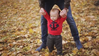 the baby learns to walk. Mom and Dad help his son to take the first steps