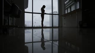 The ballerina in the studio warms up, the silhouette is reflected in the mirror floor
