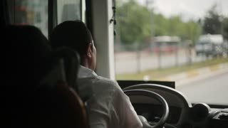 The bus driver is driving along the road.