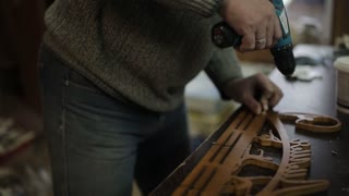 The carpenter's workshop fastens with a screwdriver and drill the hangers to the holder of medals