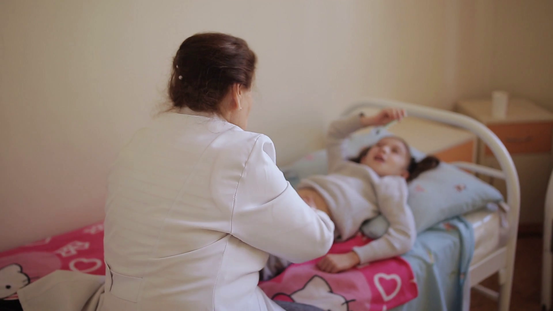 The elderly woman masseur doing massage of the abdomen to the little girl in the hospital. Stock Video Footage - Storyblocks