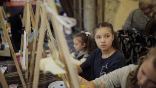 The girl is painting a picture in a children's studio of fine art. School of early development.