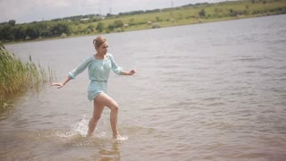 The merry girl runs along the water in the river. Romance, youth and a honeymoon. Lovers Boy and girl hugging in water