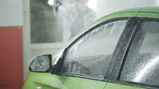 The process of washing the car in a special room with water and foam